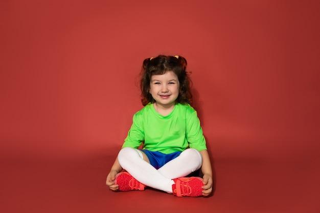 Kind sitzt mit gekreuzten beinen. sportuniform. fußballklassenkonzept für mädchen