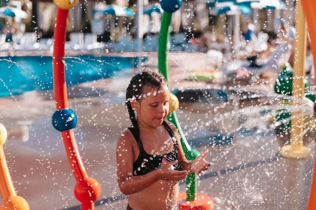 Kind spielt am pool kleines mädchen im schwarzen badeanzug sitzt am pool und spielt mit wasserstrahl...