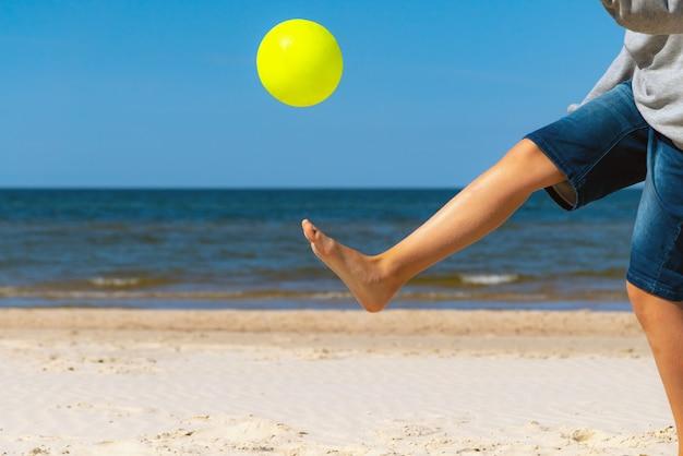 Kind spielt an einem sonnigen tag mit strandball auf dem sand am meerwasser