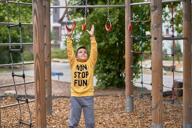 Kind spielt auf der schaukel im park