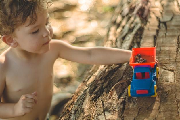 Kind spielt im freien. kind, wir gießen den sand in den roten lastwagen. kinder straßenspiele. ein junge spielt mit einer maschine auf dem großen baumstamm