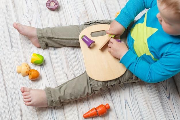 Kind spielt im koch. satz von spielzeug aus holz gemüse