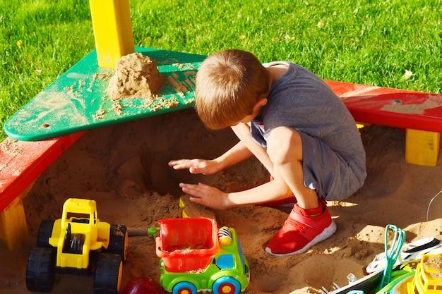 Kind spielt im sandkasten draußen