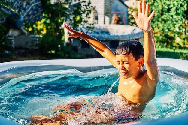 Kind spielt in einem aufblasbaren pool im hausgarten