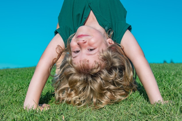 Kind spielt kopfüber auf der wiese. glücklicher gesunder kaukasischer kinderjunge mit dem lügen auf dem grasfeldhintergrund kleines kind in schöner grüner umgebung. erstaunlich glückliche kinder.