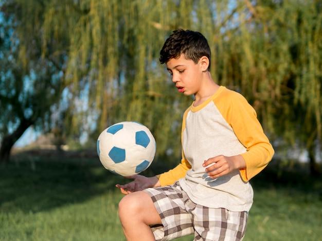 Kind spielt mit ball im freien