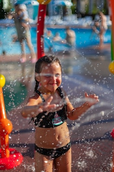 Kind spielt mit dem wasserstrahl, attraktion kleines mädchen im badeanzug mit wassermelonenbild und glas...