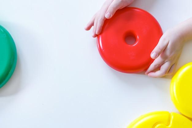 Kind spielt mit details aus der pyramide. runde mehrfarbige details vom spielzeug auf weißer wand. entwicklung der feinmotorik, lernspiele