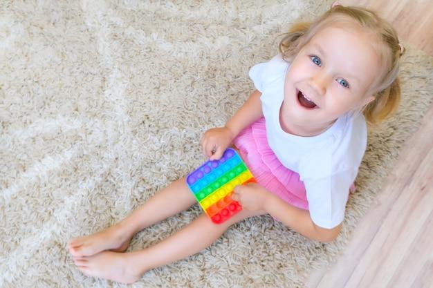 Kind spielt mit einem flatternden zappeln. beliebtes flexibles sensorisches spielzeug für kinder entwickelt feinmotorik, antistress, kann für das training mit autisten verwendet werden, popit-spielzeug