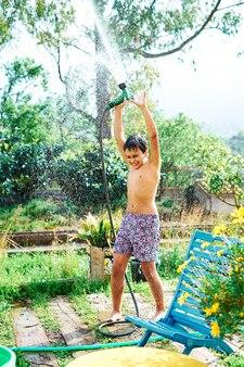 Kind spielt mit einem schlauch im hausgarten