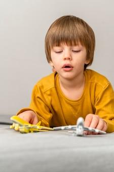 Kind spielt mit flugzeugfiguren