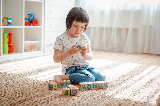 Kind spielt mit holzklötzen mit buchstaben auf gebäude-turm-ausgangskindergarten des bodenraumes des kleinen mädchens.