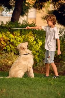 Kind spielt mit hund mit stock