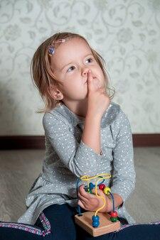 Kind spielt mit labyrinth. kleines mädchen, das mit einem finger nahe dem mund denkt. pädagogisches spielzeug.