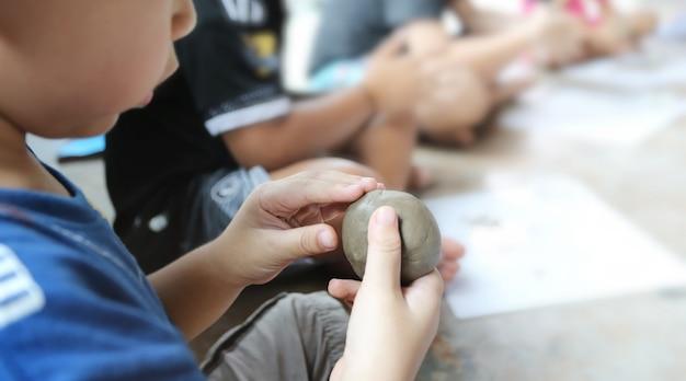 Kind spielt mit lehm. kreative aktivitäten für kinder, ausbildung in kunst.