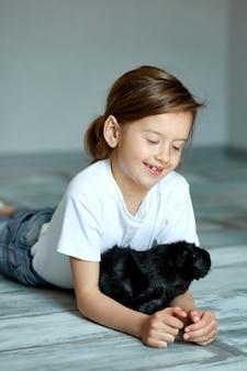 Kind spielt mit meerschweinchen. mädchen kümmern sich um haustiere.