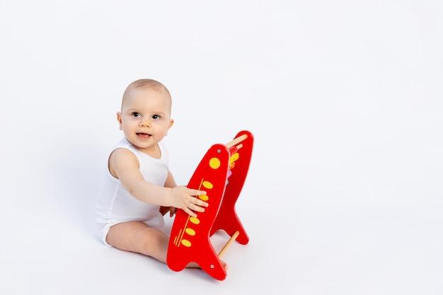 Kind spielt mit rechnungen auf einer weißen, frühen entwicklung, bis zu einem jahr,
