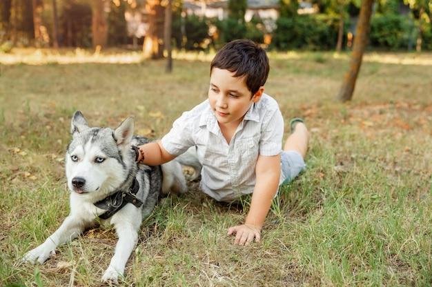 Kind spielt mit seinem welpen im park. kleiner junge, der mit hund geht