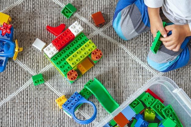 Kind spielt mit spielzeugblöcken, die auf dem boden sitzen