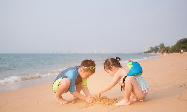 Kind spielt sand am strand, kinder spielen im meer