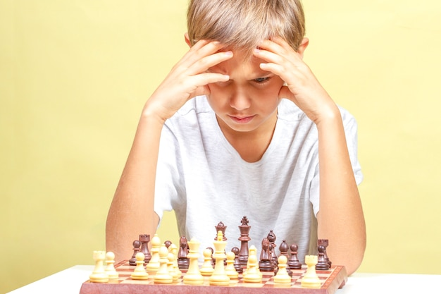Kind spielt schach. junge, der schachbrett betrachtet und über seine strategie nachdenkt.