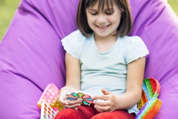 Kind spielt trendiges beliebtes brettspiel anti-stress-spielzeug pop it oder einfache grübchen di