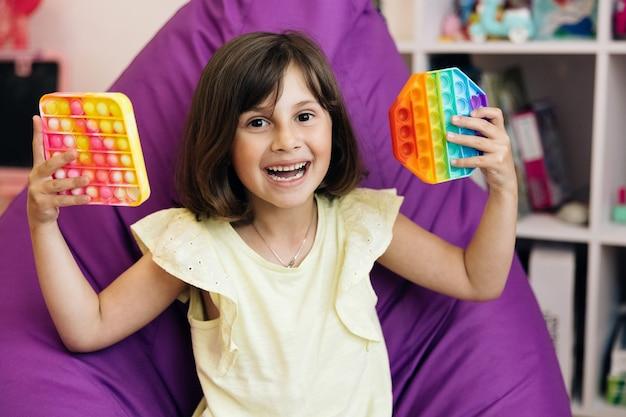 Kind spielt trendiges, beliebtes brettspiel anti-stress-spielzeug pop it popit oder einfaches grübchen