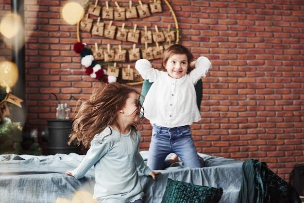 Kind springt vom sofa. kleine mädchen, die spaß auf dem bett mit feiertagsinnenraum am hintergrund haben