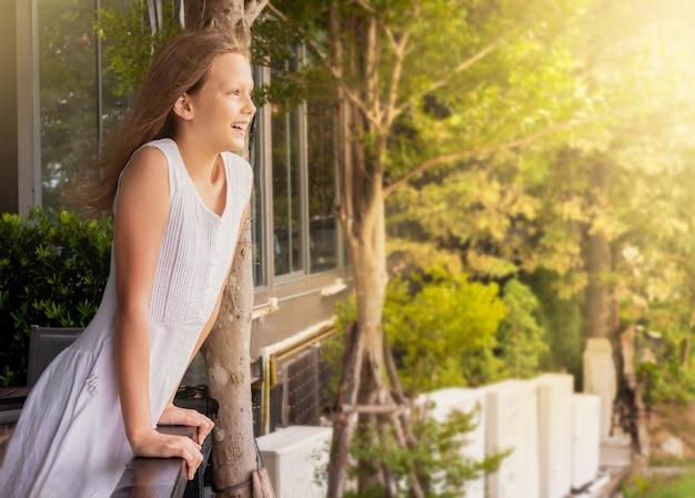 Kind steht auf dem balkon und schaut in die ferne