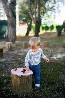 Kind steht in der nähe eines baumstumpfes in einem grünen park und neigt seinen kopf darüber over