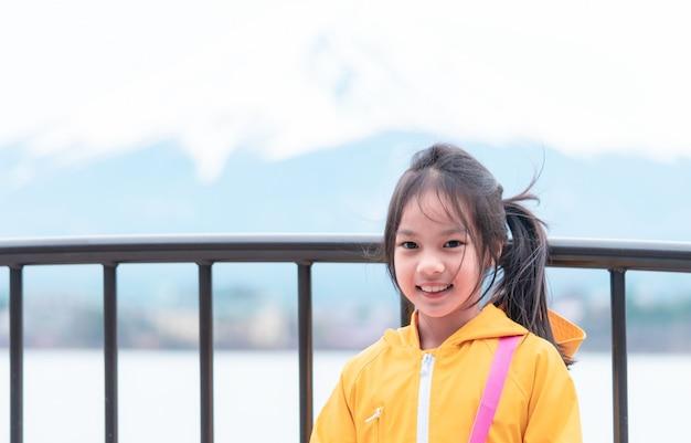 Kind steht vor kawaguchiko see und fujisan im winter.