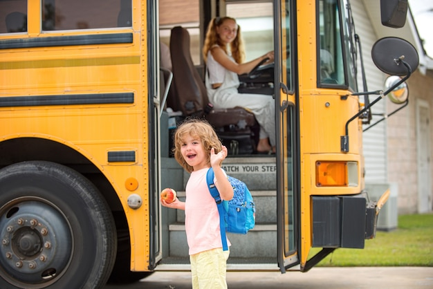 Kind steigt in schulbus ein. zurück zur schule und glückliche zeit. wenig bereit zu studieren. heimerziehung.