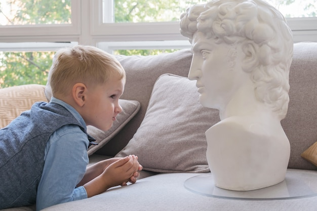 Kind studiert die struktur des gesichts mit gipsfigur