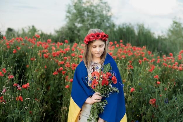 Kind trägt flatternde blaue und gelbe flagge der ukraine im mohnfeld. unabhängigkeitstag der ukraine. flagge tag.
