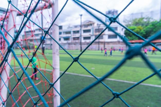 Kind trainiert fußball fußball in unscharfem hintergrund hinter dem netz