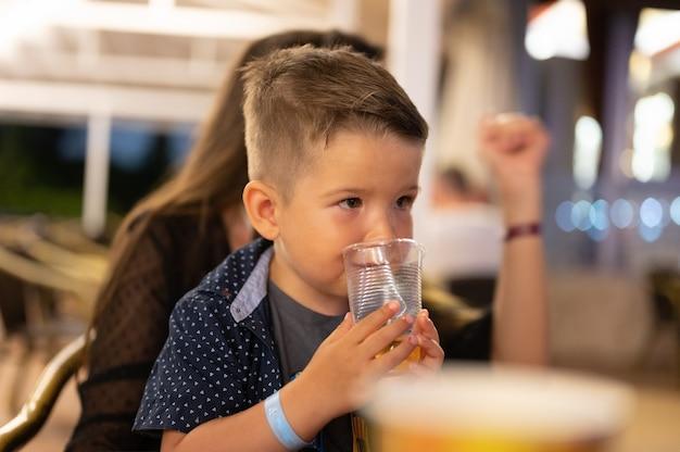 Kind trinkt ein glas wasser in einer berghütte. foto in hoher qualität