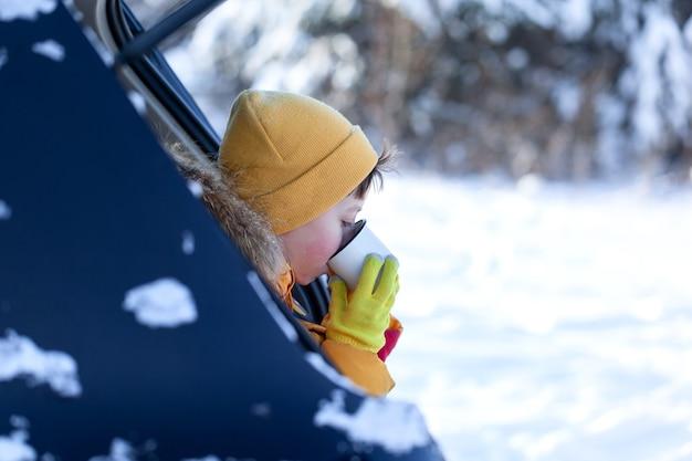 Kind trinkt heiße schokolade oder kakao beim sitzen im schwarzen auto am verschneiten wintertag. aufenthalt, reisen, tourismus im winter.