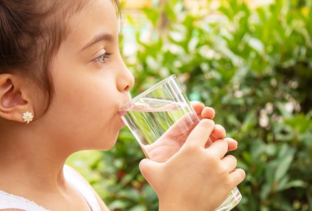 Kind trinkt reines wasser in der natur.selectiv fokus.nature