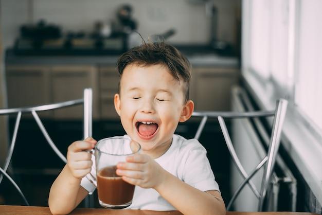 Kind trinkt tagsüber in der küche windende schokolade, hält einen becher in den händen und schreit