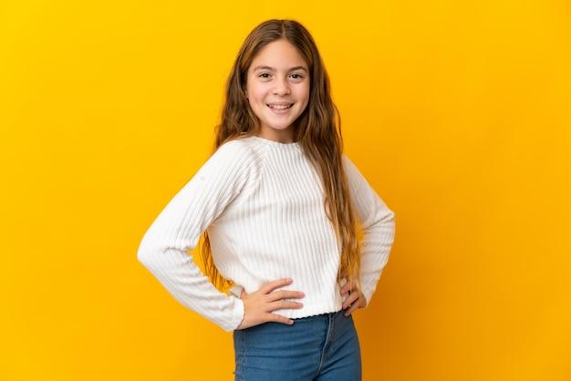Kind über isolierte gelbe wand, die mit armen an der hüfte aufwirft und lächelt