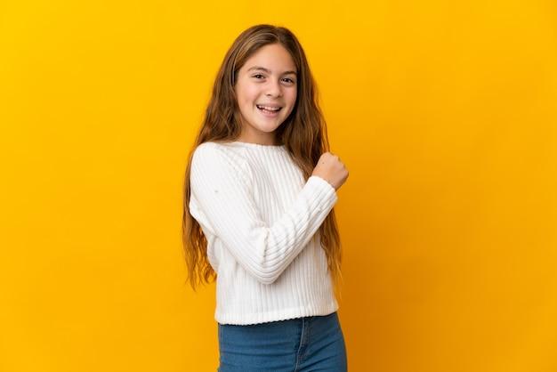 Kind über isoliertem gelb, das einen sieg feiert