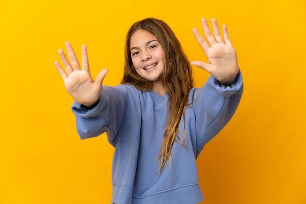 Kind über isoliertem gelb, das zehn mit den fingern zählt