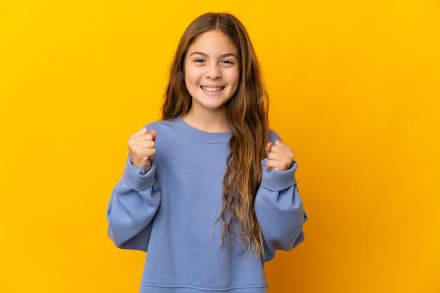 Kind über isoliertem gelbem hintergrund feiert einen sieg in siegerposition