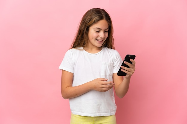 Kind über isoliertem rosa hintergrund, das eine nachricht oder e-mail mit dem handy sendet sending