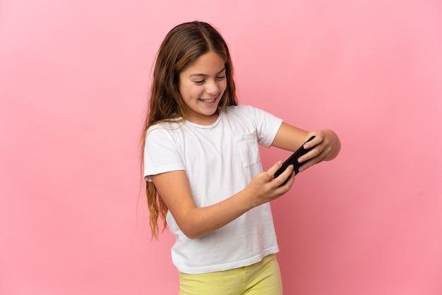 Kind über isoliertem rosa hintergrund, das mit dem handy spielt