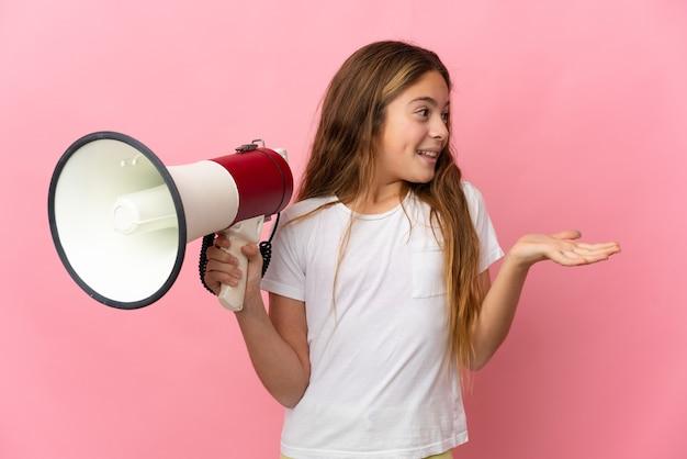 Kind über isoliertem rosa hintergrund mit megaphon und überraschtem gesichtsausdruck