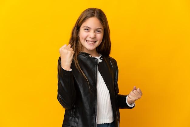 Kind über isolierter gelber wand, die einen sieg feiert