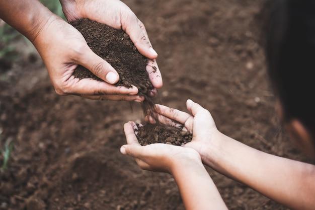 Kind und elternteil, die boden halten und boden für das zusammenpflanzen des baums vorbereiten