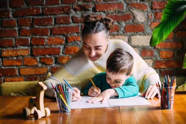Kind und erwachsener zeichnen ein malbuch