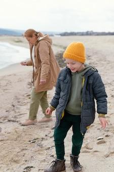 Kind und frau am strand voller schuss